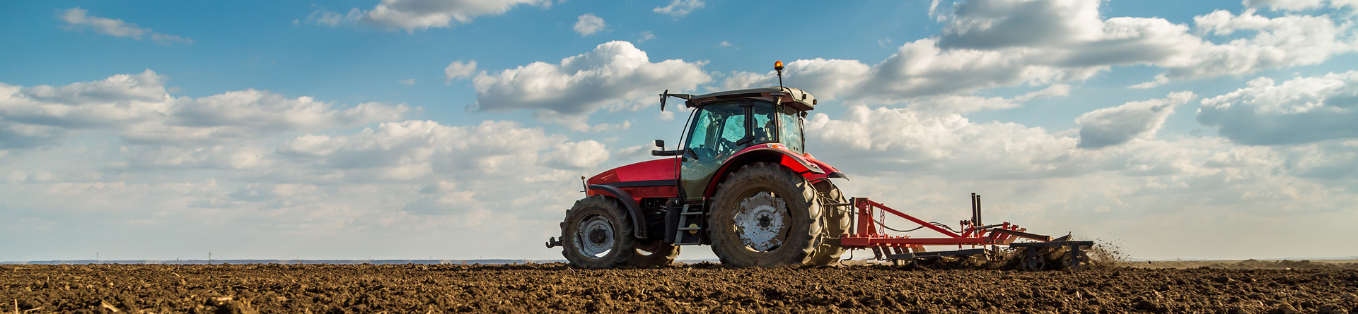 Farmer on cultivator preparing fields for planting
