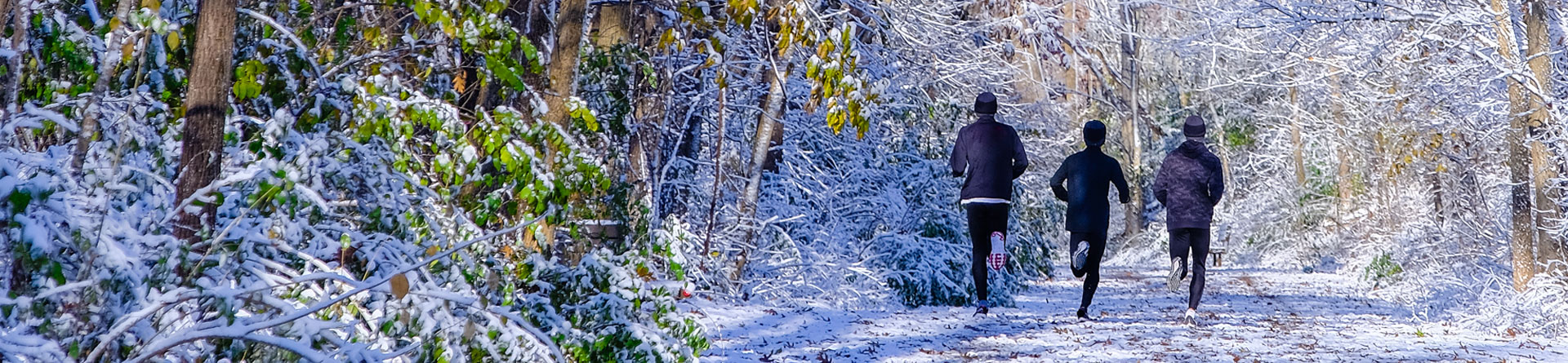Men jogging along snowy path on a trail