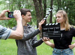 A teen boy holding a clapboard in front of a girl while someone in the foreground films them