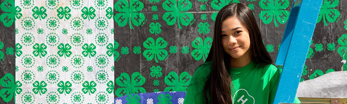 A young woman posing in front of a 4-H wall