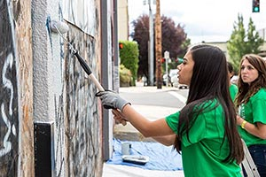 4-H volunteers painting over grafitti.