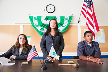 4-H club members sit at a table during a meeting.