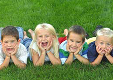 Four happy kids lying on the grass.