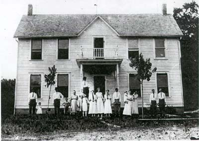 Old photo of farmhouse with inhabitants standing outside