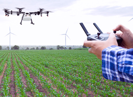 Farmer operating a drone over fields