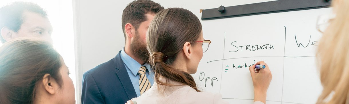 Business colleagues creating list on dry erase board