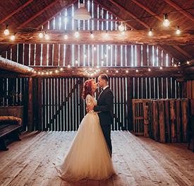 A couple posing in a barn for wedding photos