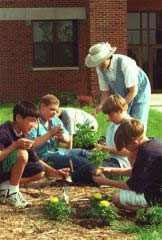 An adult leader working with kids in a garden plot
