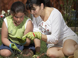 Girl gardening with adult