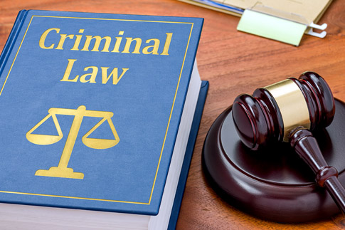 A criminal law code book sits next to a gavel on a desk.