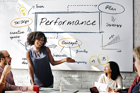 A woman gives a presentation in front of a white board with performance written on it.
