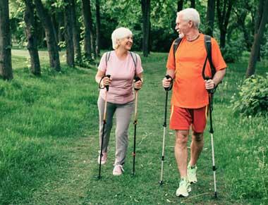 Senior couple walking in woods using walking sticks