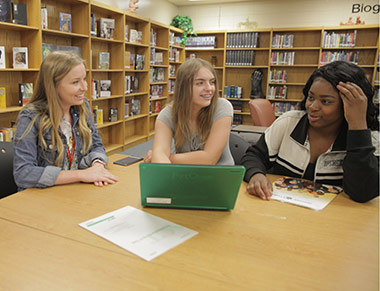 College adviser meeting with two students in a school library.