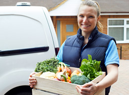 Woman delivering a box of vegetables.
