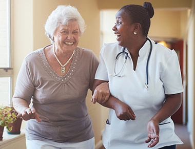 An elderly woman and a female nurse laugh as they walk arm and arm down a hallway.