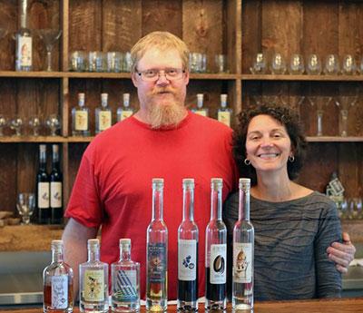 Jim Pierce and Sarah Burnett Pierce pose at the bar in Of the Earth Farm Distillery.