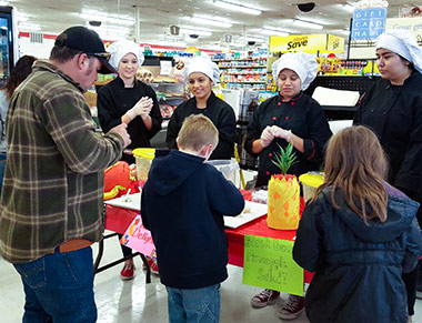 A family samples food at a grocery store.