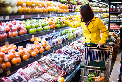 A woman pushing her cart down the produce isle of a grocery store while examing the produce.