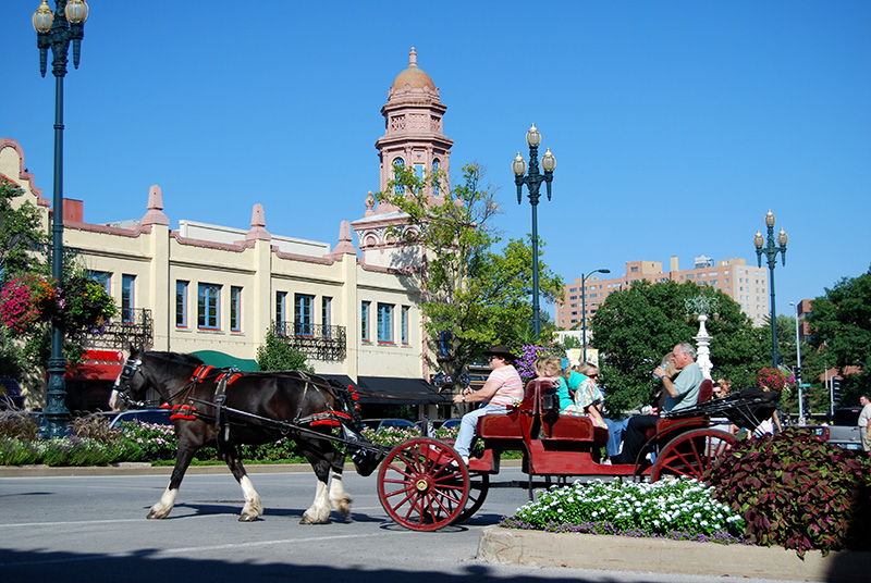 A horse drawn carraige with passengers passes through a scenic downtown area.